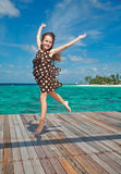 Little girl dancing on the wooden sundeck. Little blond girl dancing on the wooden sun deck and smiling royalty free stock photos