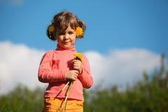 Little girl with dandelion against sky Stock Image