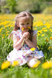 Little girl on dandelion field Stock Image