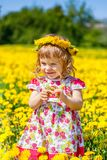 Little girl on the dandelion field Royalty Free Stock Image
