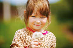 Little girl with dandelion Stock Image