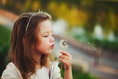 Little girl with dandelion in park Royalty Free Stock Photos