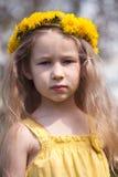 Little girl in dandelion wreath. Portrait of little fair-haired girl in dandelion wreath Royalty Free Stock Photography