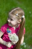 Little girl with dandelions. Smiling little girl on a green meadow with a bouquet of dandelions Royalty Free Stock Photography