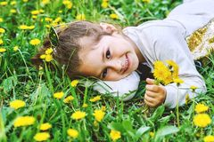 Funny girl with dandelions lying on the grass royalty free stock photos