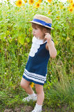 Girl in a dark blue dress near a field of blossoming sunflowers Royalty Free Stock Images