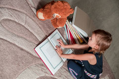 little girl in  dark blue dress reading  book sitting on the floor near teddy bear. Child reads story for toy. Stock Photos