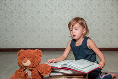 little girl in  dark blue dress reading  book sitting on the floor near teddy bear. Child reads story for toy. Royalty Free Stock Photography