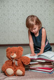 little girl in  dark blue dress reading  book sitting on the floor near teddy bear. Child reads story for toy. Royalty Free Stock Image