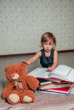 Little girl in  dark blue dress reading  book sitting on the floor near teddy bear. Child reads story for toy. Royalty Free Stock Photos