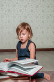 Little girl in  dark blue dress reading  book sitting on the floor near teddy bear. Child reads story for toy. Turns the page. Stock Photo