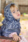 The little girl in a dark blue kerchief Stock Photography