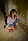 Little girl in a dark cellar Stock Photography