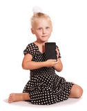 Little girl in dark dress with polka dots, holding mobile. Little girl in a dark dress with polka dots, holding a mobile while sitting isolated on white stock photography
