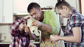 Little girl and elder sister help father to prepare dough. Little girl with dark hair and elder sister with down syndrome help father to prepare delicious dough stock footage