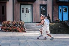 Dark-haired little girl wearing white dress and fairy wings skateboarding royalty free stock photo
