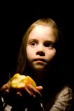 Little girl in the darkness. Holding apple in her hands Stock Photography