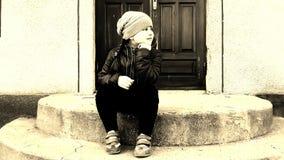 Little girl Dasha sitting on stairs Stock Image