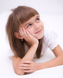Little girl is daydreaming. Lying on the floor Stock Photography