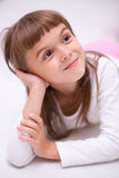 Little girl is daydreaming. Lying on the floor Stock Images