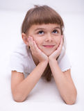 Little girl is daydreaming. Lying on the floor Royalty Free Stock Images
