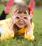 Little girl is daydreaming. Lying on green grass Stock Images