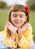 Little girl is daydreaming. Lying on green grass Royalty Free Stock Photo