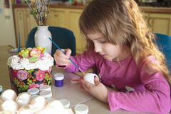 Little girl decorated eggs for Orthodox Easter during quarantine
