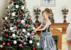 Little girl decorates the Christmas tree . Stock Photos