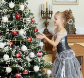 Little girl decorates the Christmas tree . Royalty Free Stock Photo
