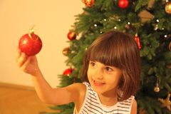 Little girl decorates Christmas tree. Little girl in blue and white dress decorates Christmas tree stock image