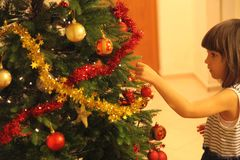 Little girl decorates Christmas tree. Little girl in blue and white dress decorates Christmas tree royalty free stock photography