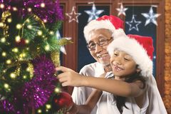 Little girl decorates Christmas tree with her grandpa Royalty Free Stock Photo