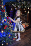 Little girl decorates   Christmas tree Royalty Free Stock Photo