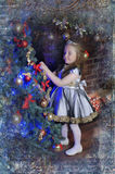 Little girl decorates   Christmas tree Stock Images