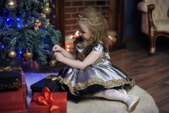 Little girl decorates   Christmas tree Stock Photos