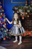 Little girl decorates   Christmas tree Royalty Free Stock Images