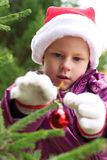 Little girl decorates a Christmas tree on the street Stock Images