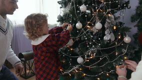 Little girl decorates a Christmas tree stock video