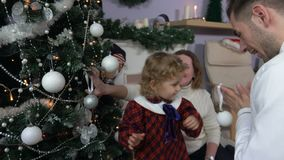 Little girl decorates a Christmas tree stock footage