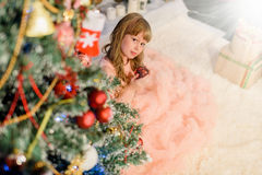 Little girl decorates christmass tree.  Stock Photo