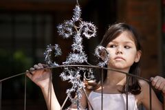 Little girl decorates the gate of the house. The Little girl decorates the gate of the house stock image