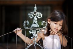 Little girl decorates the gate of the house. The Little girl decorates the gate of the house royalty free stock image