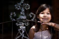 Little girl decorates the gate of the house. The Little girl decorates the gate of the house stock photography