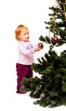 A little girl decorates a new-year tree Stock Image
