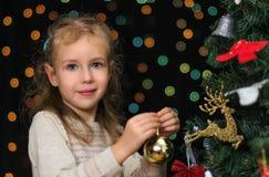 Little girl decorates tree Royalty Free Stock Photo