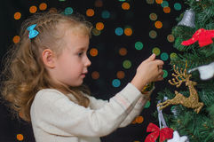 Little girl decorates tree Royalty Free Stock Photography