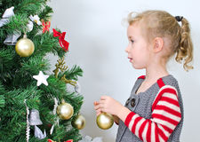 Little girl decorates tree Royalty Free Stock Image