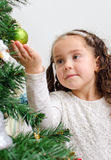 Little girl decorates tree Stock Photos