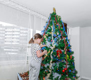 Little girl decorating big christmass tree in grey room Royalty Free Stock Image